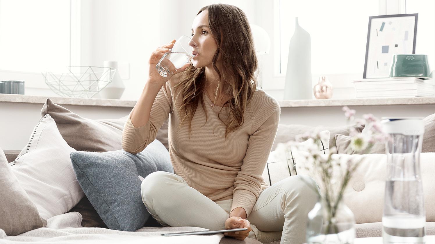 BRITA Wasserbedarf Frau Couch trinkt Wasser