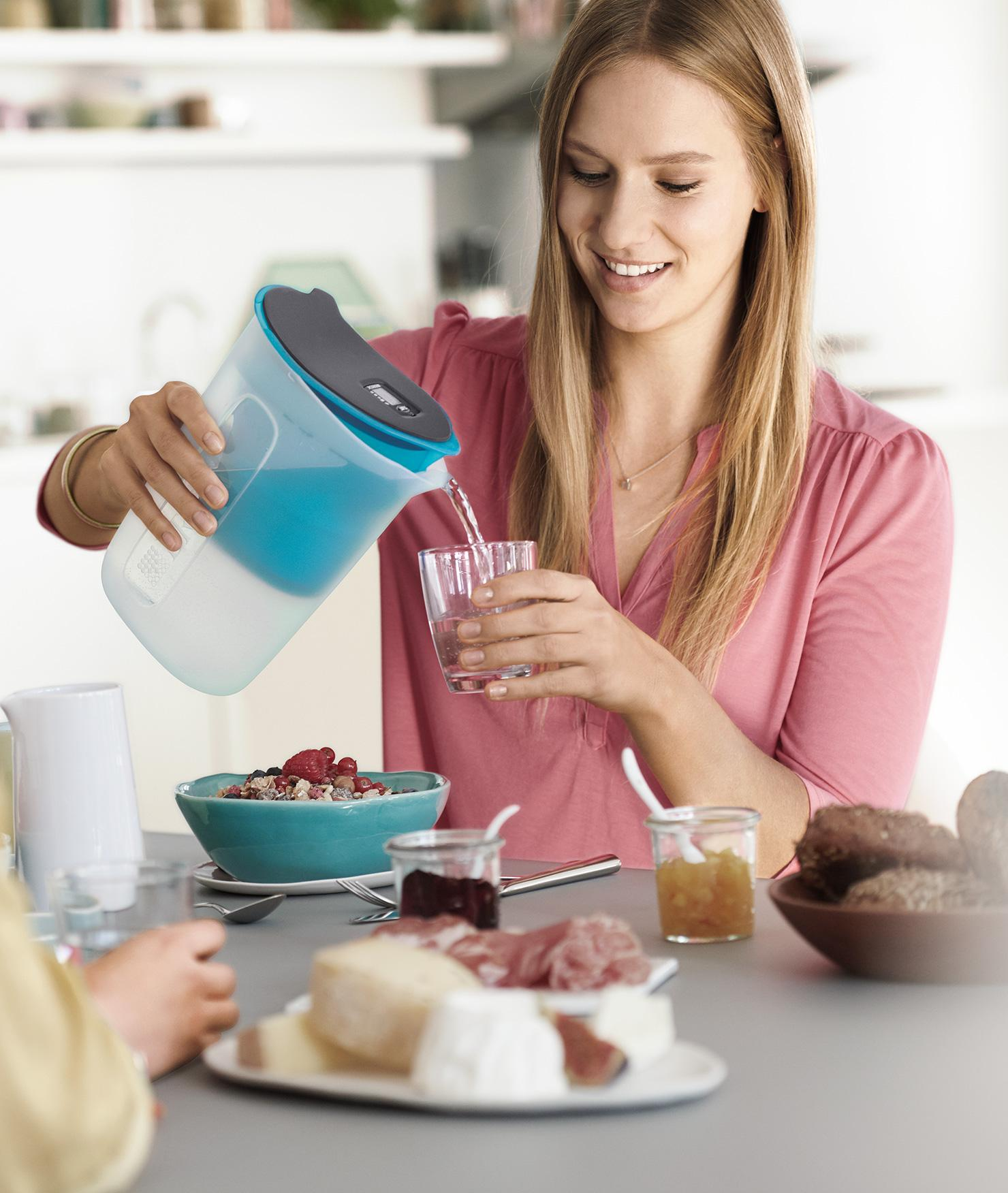 BRITA fill&enjoy Fun pink: Frau in Küche trinkt