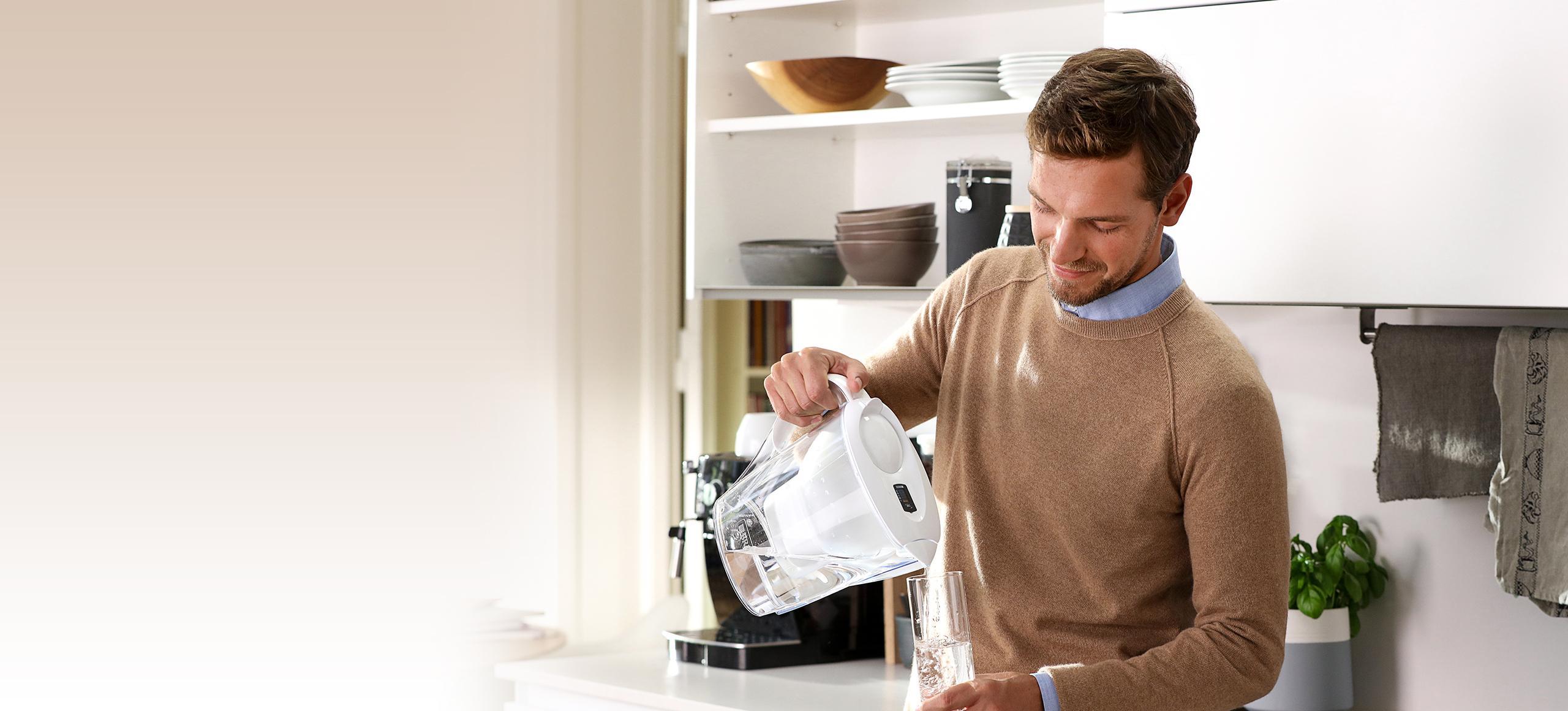 Homme dans la cuisine qui utilise une carafe filt