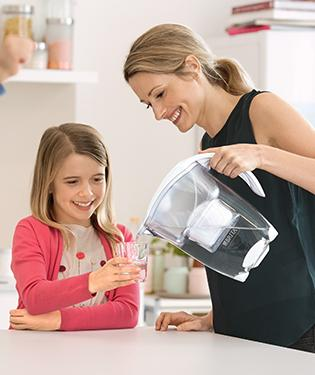 Mother pouring water from jug with daughter