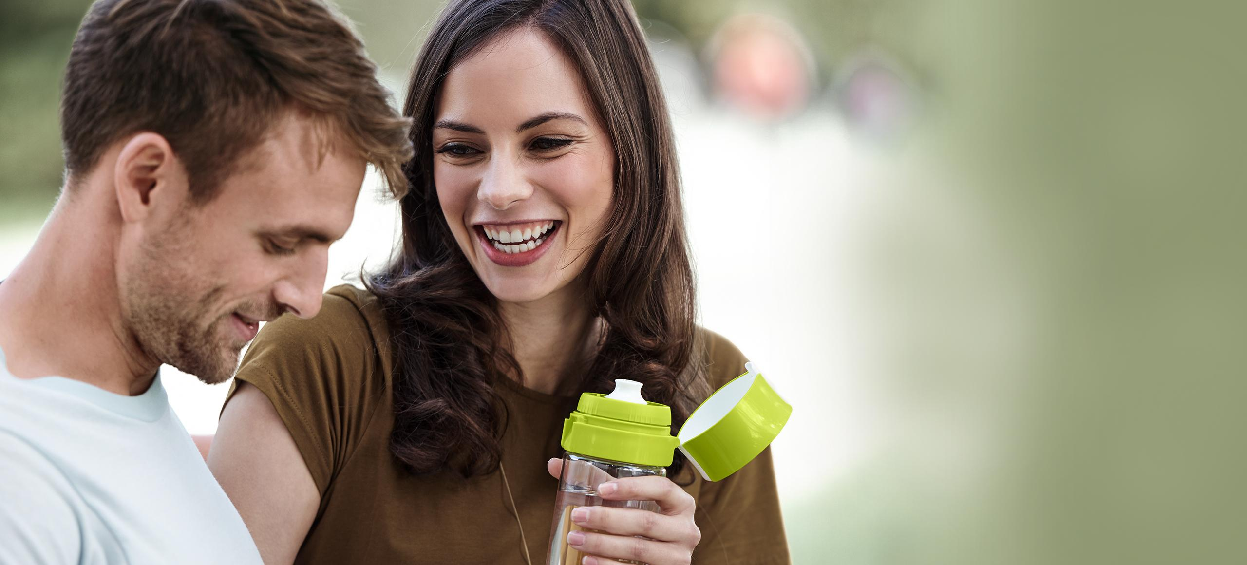 Laughing couple with woman holding fill&go bottle
