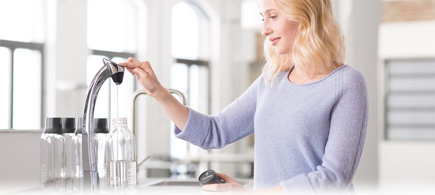 woman fills wave water bottle from water dispenser