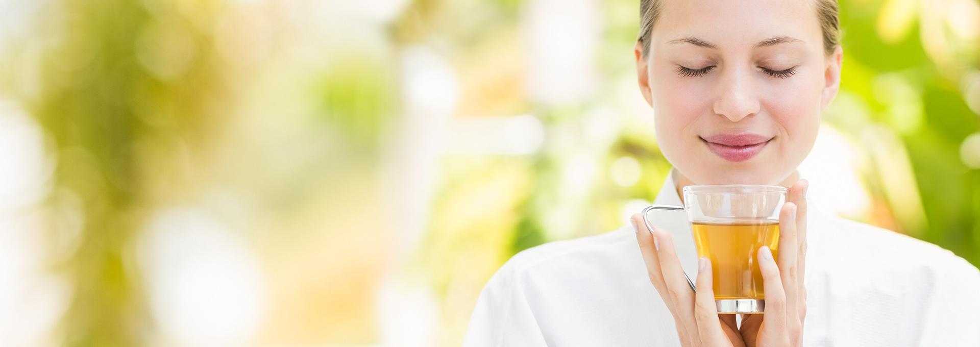 Frau genießt Tasse Tee mit gefiltertem Wasser
