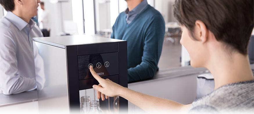 Woman drawing filtered water from water dispenser