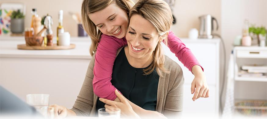 Mother and daughter laughing at kitchen table