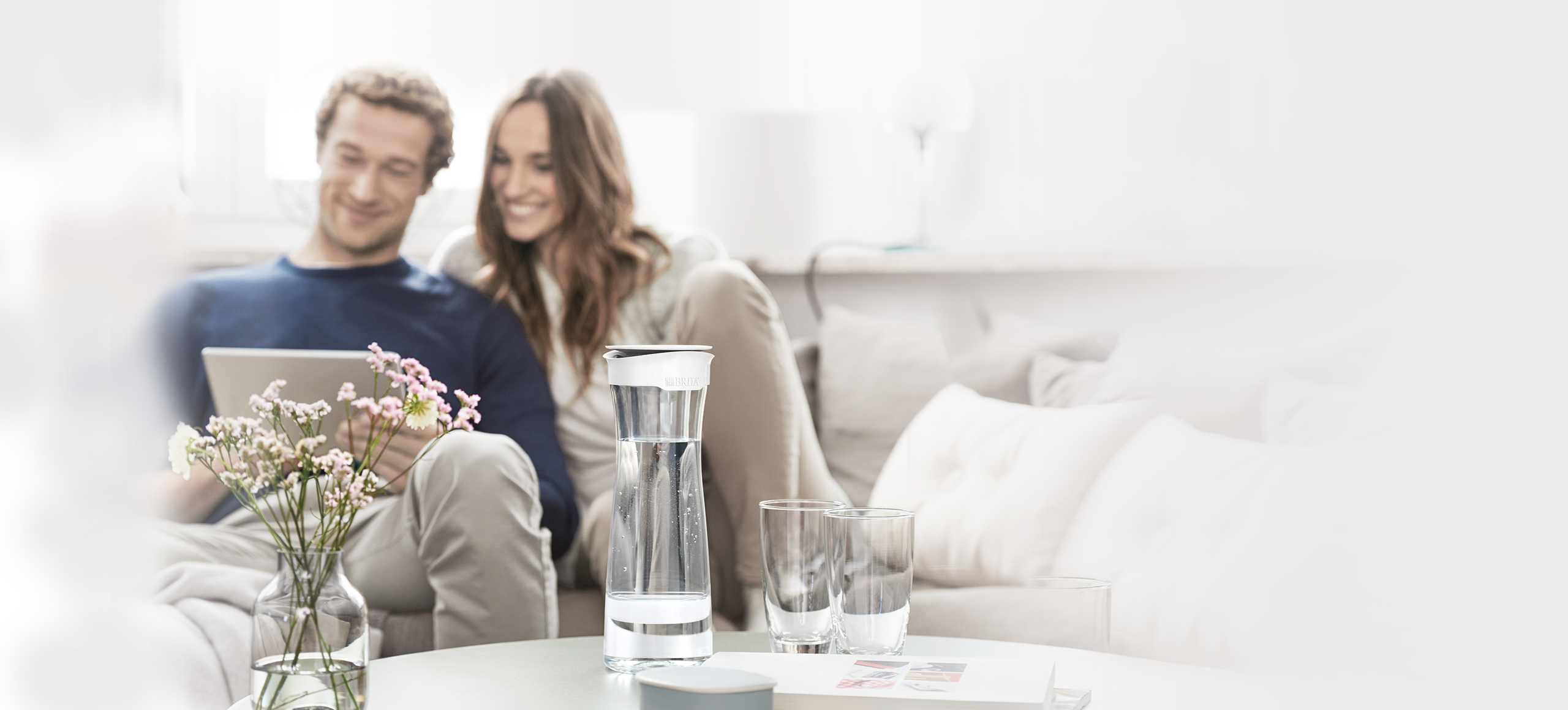 坐在客廳使用平板電腦的情侶