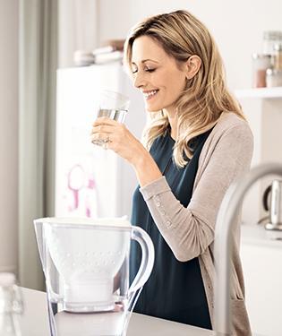 正使用 Marella 濾水壺喝水的女士