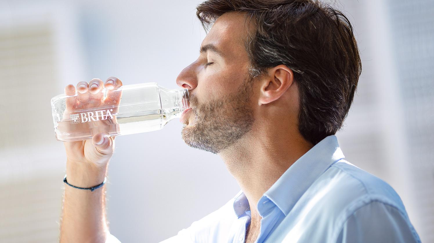 Mann trinkt zufrieden Wasser