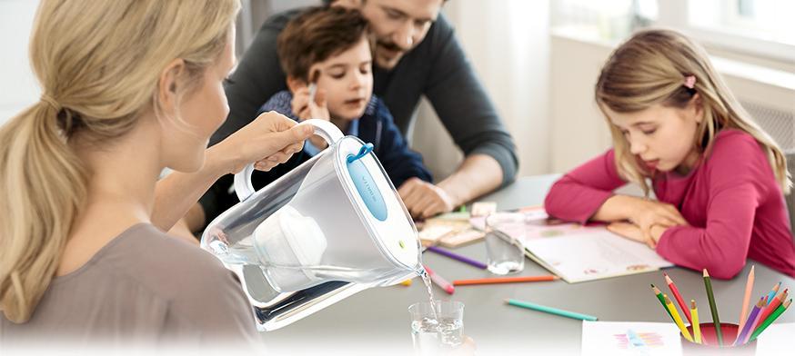 女士在家中餐桌上使用 Style 智型濾水壺倒水