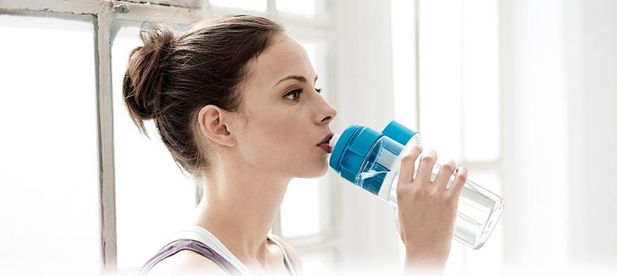 Woman drinking water from fill&go bottle
