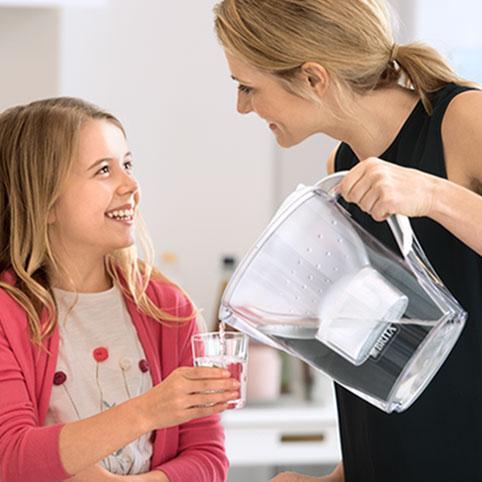 BRITA over moeder meisje in keuken schenkt water
