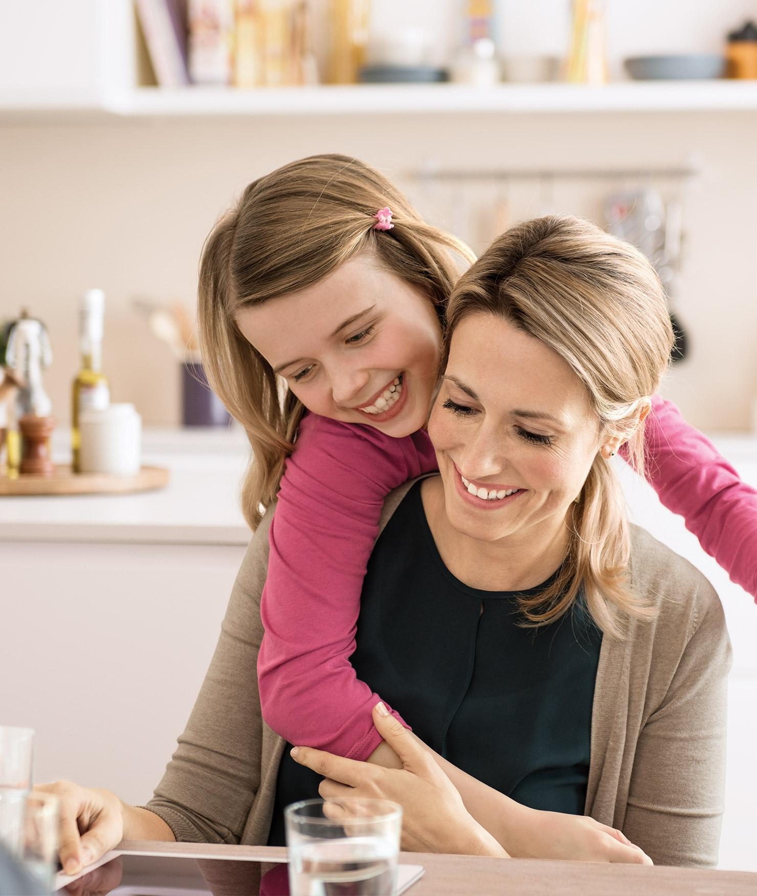 Una madre y una hija están felices en una cocina.