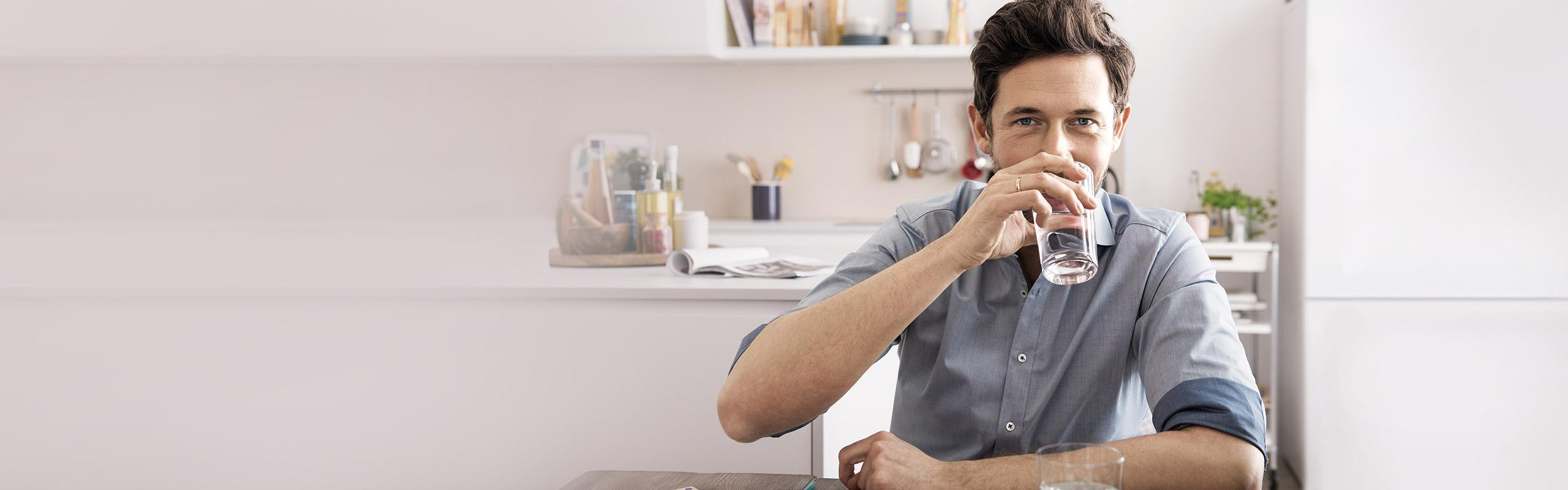 A man is sitting in a kitchen and drinking water.