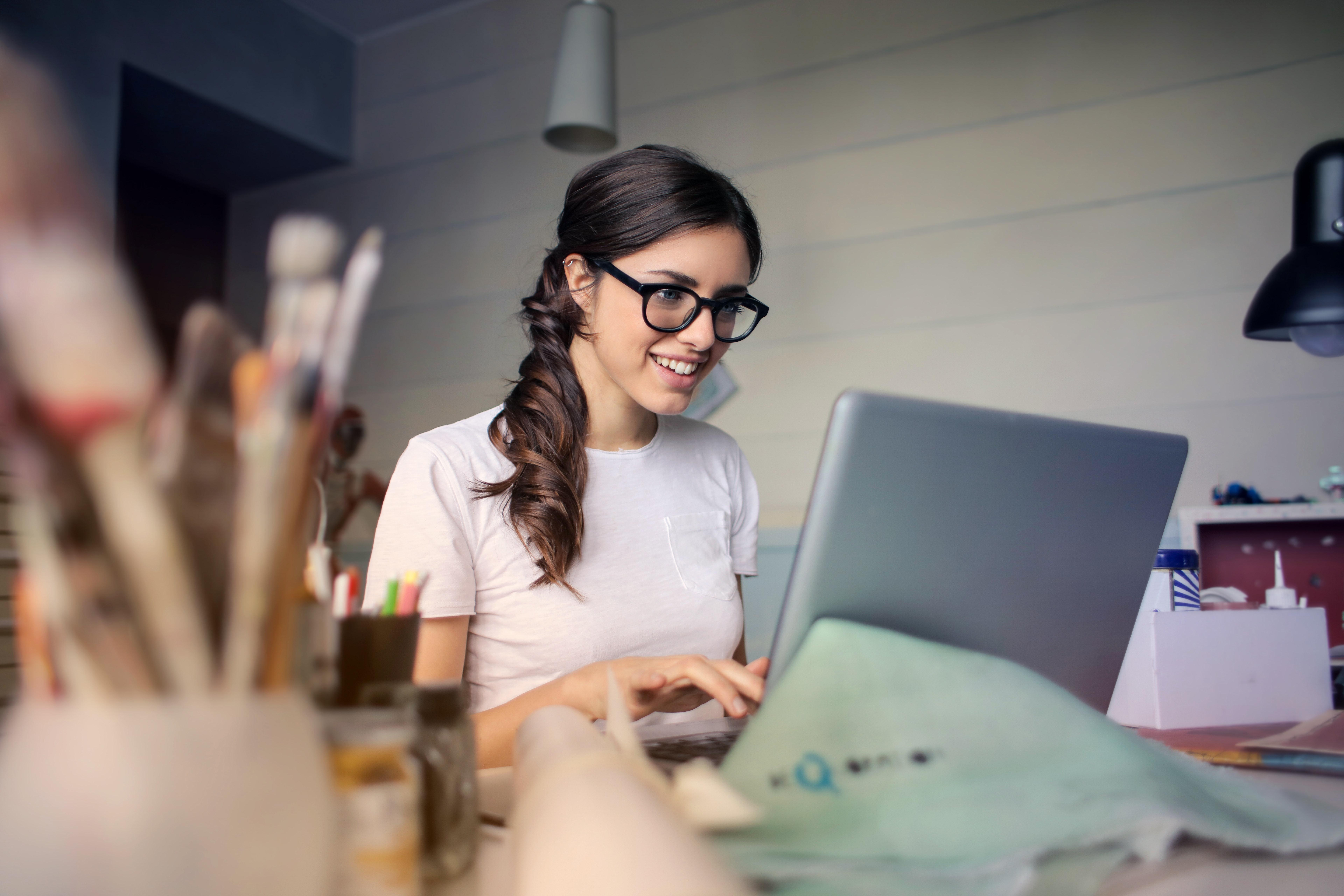 Happy Woman in office with laptop