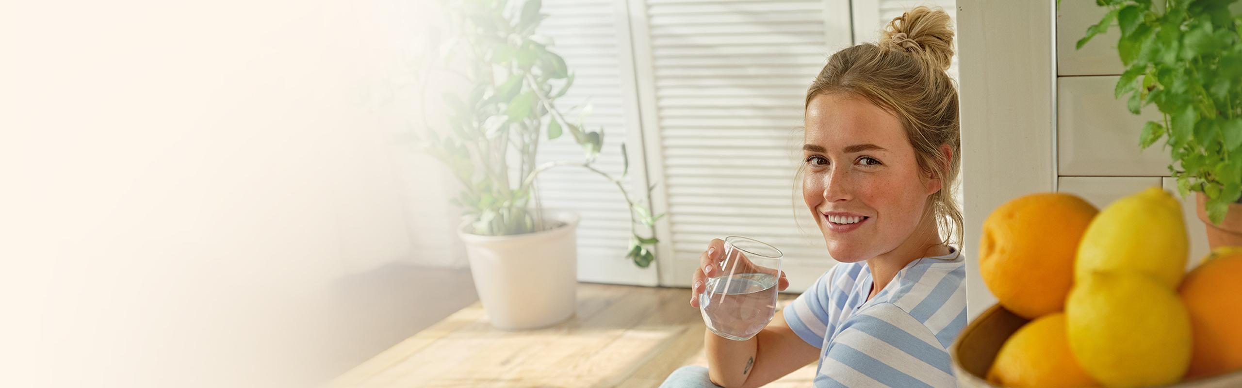 Une femme boit de l'eau filtrée BRITA
