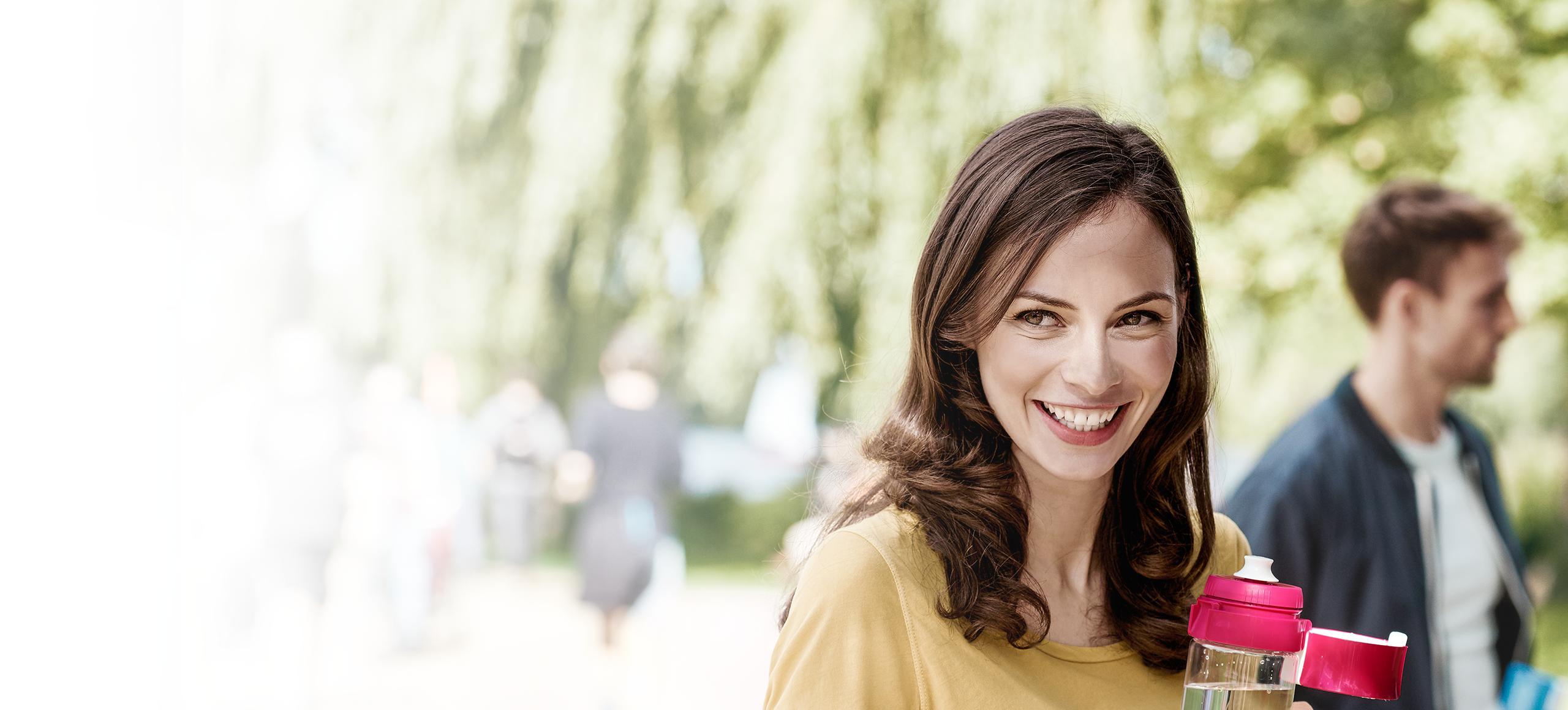 Nasmejana ženska s plastenko fill&go.