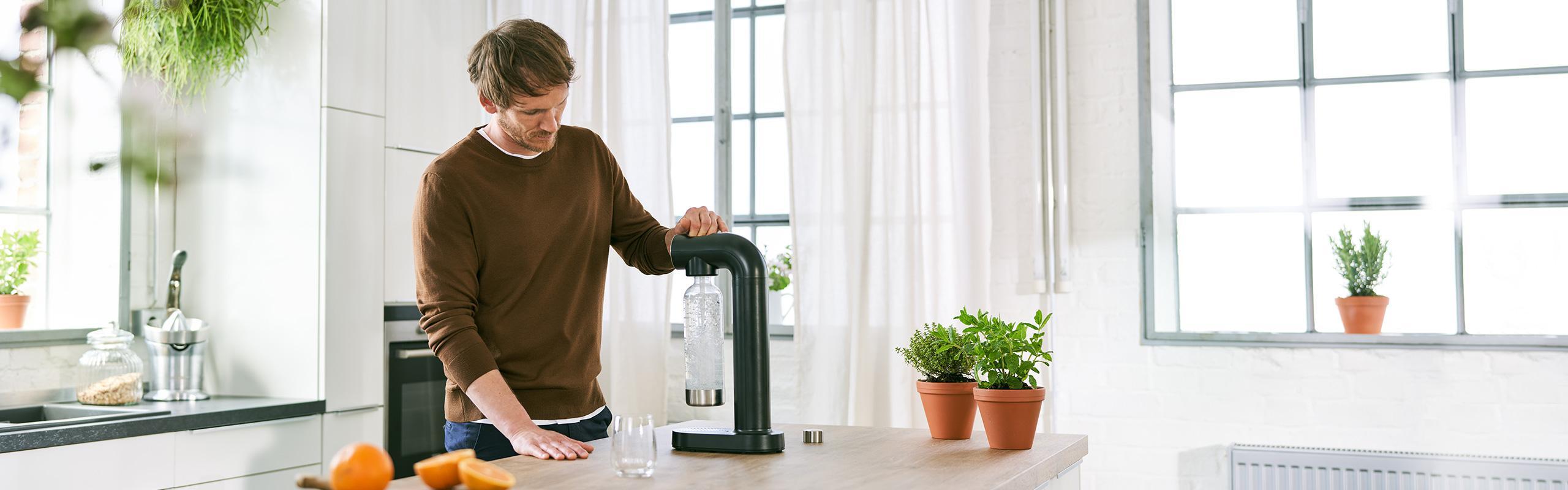 Mann in Küche mit BRITA Wassersprudler sodaONE