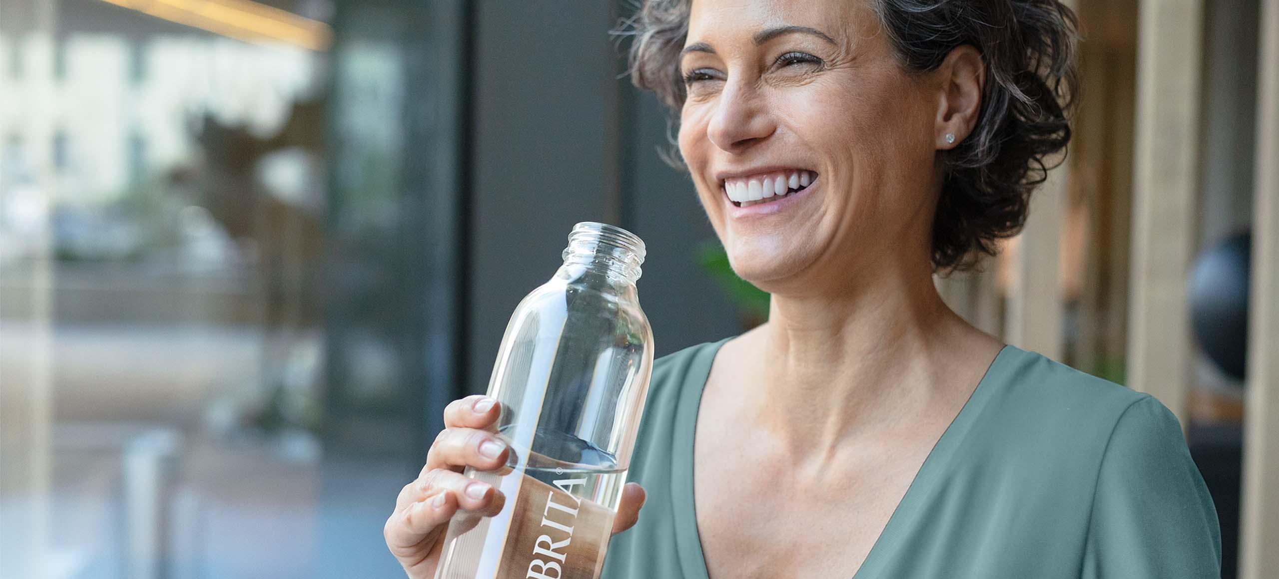 Vrouw drinkt water BRITA waterfles